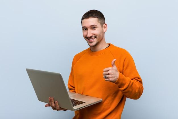 Giovane uomo caucasico che tiene un computer portatile che sorride e che alza pollice in su