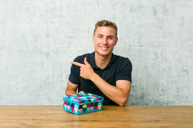 Giovane uomo caucasico che tiene un contenitore di regalo su una tavola che sorride e che indica da parte, mostrando qualcosa allo spazio in bianco.