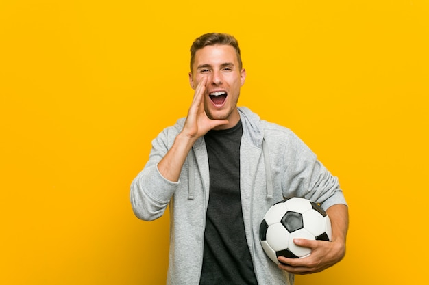 Giovane uomo caucasico che tiene un gridare del pallone da calcio eccitato alla parte anteriore.