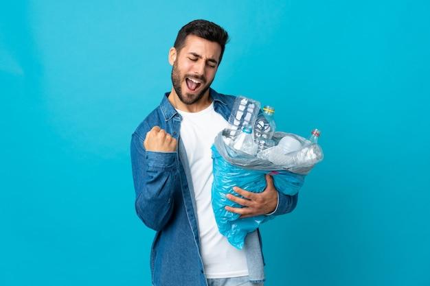 Giovane uomo caucasico che tiene un sacchetto pieno di bottiglie di plastica da riciclare isolato sulla parete blu che celebra una vittoria