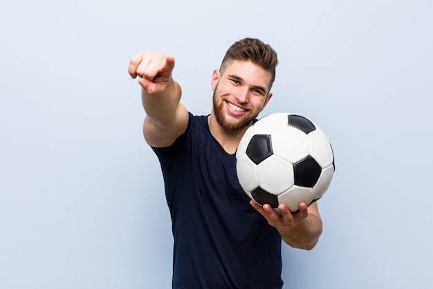Giovane uomo caucasico che tiene un sorriso allegro di un pallone da calcio che indica la parte anteriore.