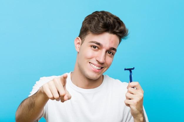 Giovane uomo caucasico che tiene una lama di rasoio sorrisi allegri che indicano la parte anteriore.