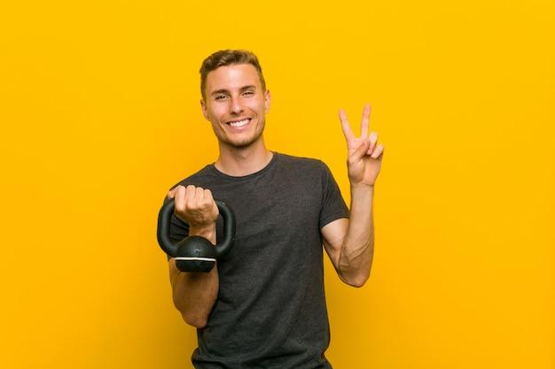 Giovane uomo caucasico che tiene una testa di legno che mostra numero due con le dita.
