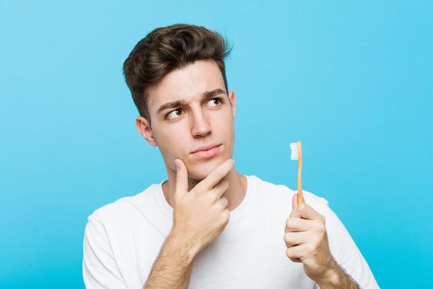 Giovane uomo caucasico che tiene uno spazzolino da denti giovane donna indiana che indossa un pigiama e una maschera per dormire isolati tenendo un cuscino guardando lateralmente con espressione dubbiosa e scettica. <mixto>