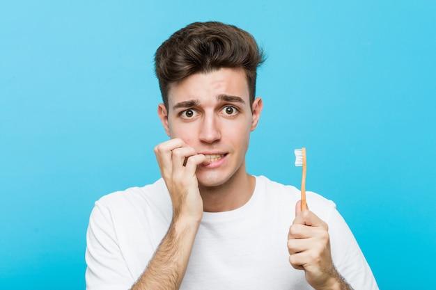 Giovane uomo caucasico che tiene uno spazzolino da denti giovane donna indiana che indossa un pigiama e una maschera per il sonno isolata tenendo un cuscino che morde le unghie, nervose e molto ansiose. <mixto>