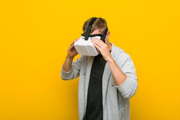 Giovane uomo caucasico che usando i vetri di una realtà virtuale