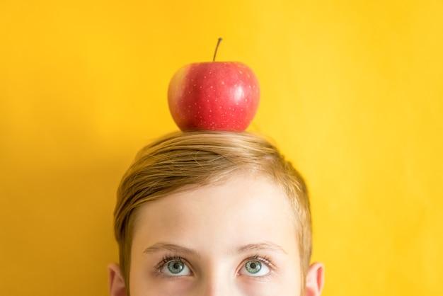 Giovane uomo caucasico con mela rossa in cima alla testa su sfondo giallo. idee eureka e concetto di sana alimentazione