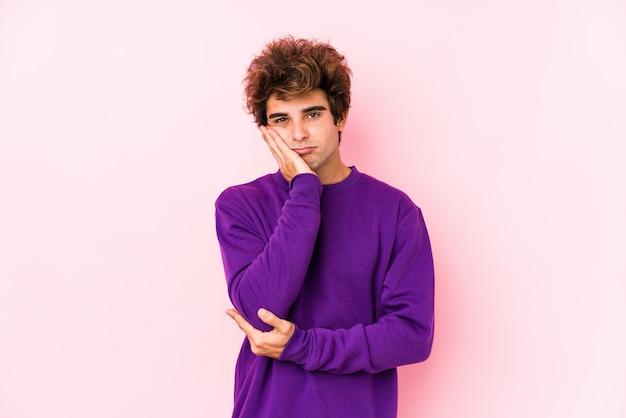 Giovane uomo caucasico contro un muro rosa isolato che è annoiato, affaticato e ha bisogno di una giornata di relax.