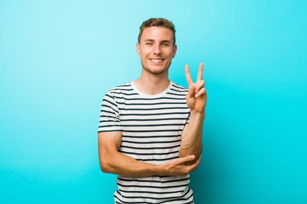 Giovane uomo caucasico contro una parete blu che mostra il numero due con le dita.
