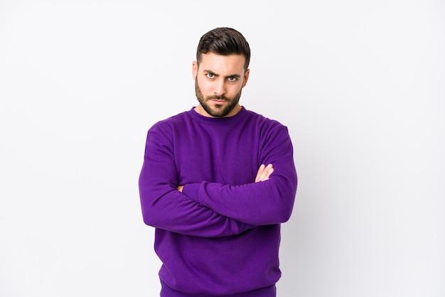 Giovane uomo caucasico contro uno sfondo bianco isolato accigliato faccia di dispiacere, mantiene le braccia conserte.