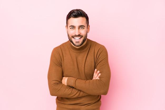 Giovane uomo caucasico contro uno sfondo rosa isolato ridendo e divertendosi.
