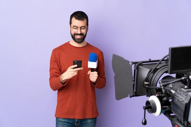 Giovane uomo caucasico del reporter sopra la parete viola isolata
