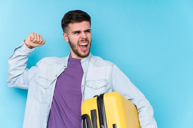 Giovane uomo caucasico del viaggiatore che tiene un pugno di sollevamento isolato valigia dopo una vittoria, concetto del vincitore.