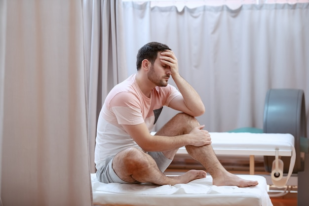 Giovane uomo caucasico depresso serio che si siede sul letto di ospedale e che tiene la sua testa.
