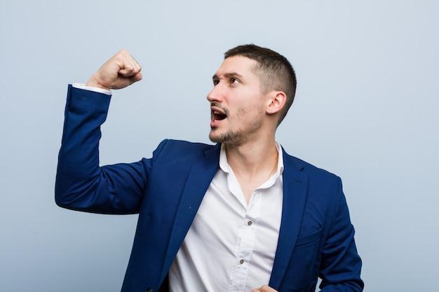 Giovane uomo caucasico di affari che alza pugno dopo una vittoria, concetto del vincitore.