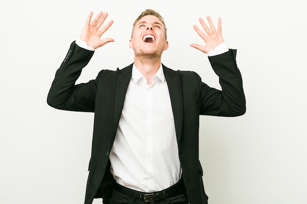 Giovane uomo caucasico di affari che grida al cielo, osservando in su, frustrato.