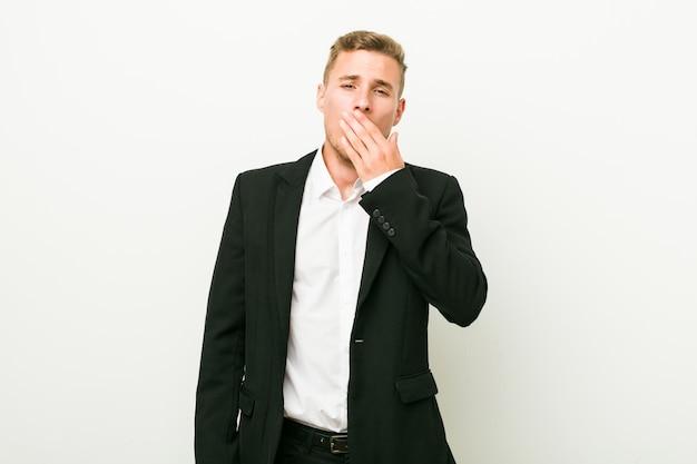 Giovane uomo caucasico di affari che sbadiglia mostrando una bocca stanca della copertura di gesto.