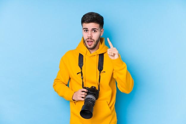 Giovane uomo caucasico fotografo isolato avendo un'idea, concetto di ispirazione.