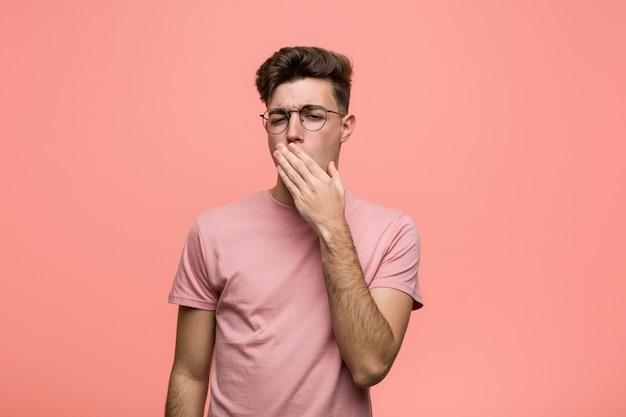 Giovane uomo caucasico freddo che sbadiglia mostrando un gesto stanco che copre la bocca con la mano