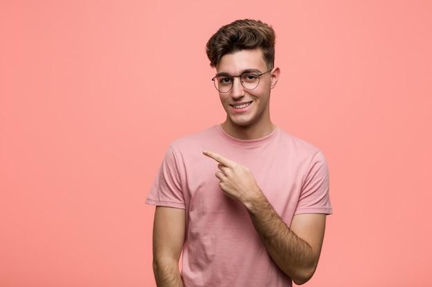 Giovane uomo caucasico freddo che sorride e che indica da parte, mostrando qualcosa allo spazio.