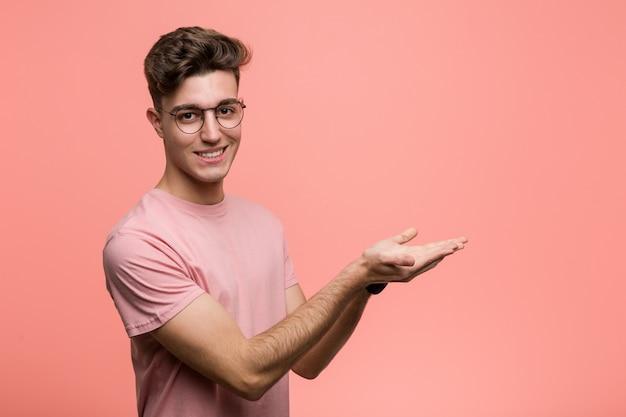 Giovane uomo caucasico freddo che tiene uno spazio della copia su una palma.