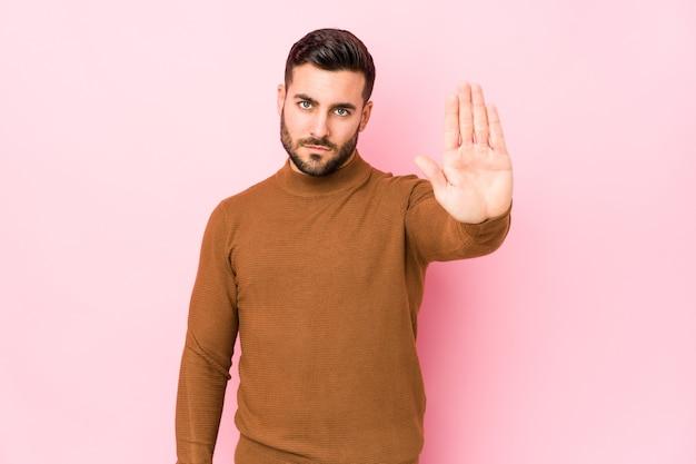 Giovane uomo caucasico in piedi con la mano tesa che mostra il segnale di stop, impedendoti.