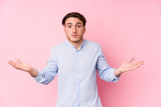 Giovane uomo caucasico in posa su rosa isolato dubitando e scrollando le spalle nel gesto interrogativo.