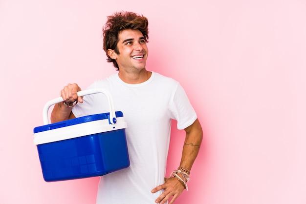 Giovane uomo caucasico in possesso di un frigorifero portatile sorridente fiducioso con le braccia incrociate.