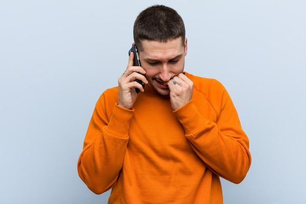 Giovane uomo caucasico in possesso di un telefono mordere le unghie, nervoso e molto ansioso.