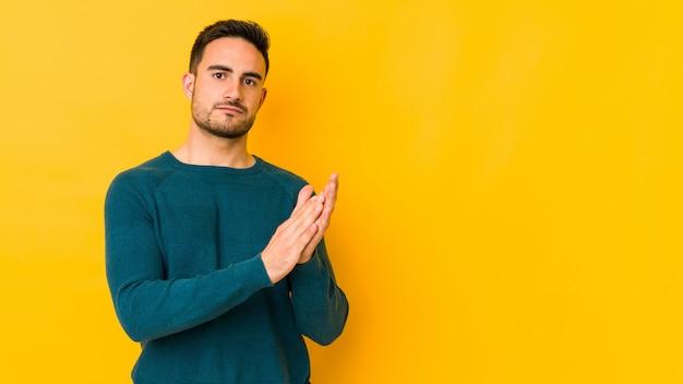 Giovane uomo caucasico isolato su bakground giallo che ritiene confidont onergetico e comodo, sfregamento delle mani.