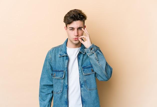 Giovane uomo caucasico isolato sul muro beige con le dita sulle labbra mantenendo un segreto.