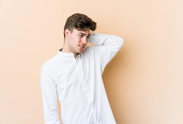 Giovane uomo caucasico isolato sul muro beige stanco e molto assonnato tenendo la mano sulla testa.