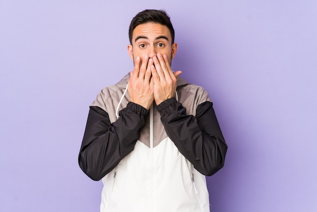 Giovane uomo caucasico isolato sulla bocca della copertura colpita viola con le mani.