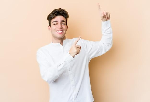 Giovane uomo caucasico isolato sulla parete beige ballando e divertendosi.