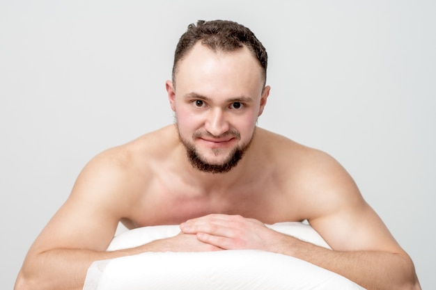 Giovane uomo caucasico sdraiato sulla parte anteriore sul tavolo spa, in attesa di un trattamento di bellezza