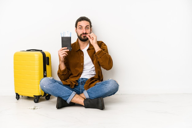 Giovane uomo caucasico seduto in possesso di un passaporto e una valigia isolata con le dita sulle labbra mantenendo un segreto.