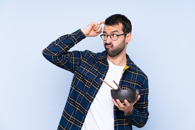 Giovane uomo caucasico sopra la parete blu che ha dubbi e con espressione del viso confuso mentre si tiene una ciotola di noodles con le bacchette