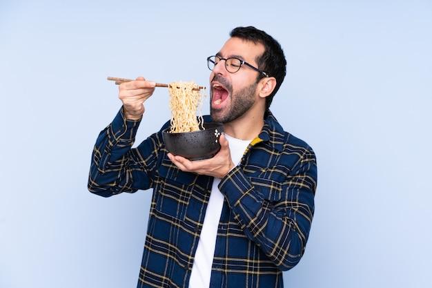 Giovane uomo caucasico sopra la parete blu che tiene una ciotola di noodles con le bacchette e mangiarlo