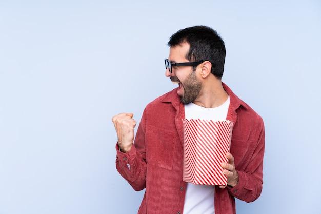 Giovane uomo caucasico sopra la parete blu con gli occhiali 3d e in possesso di un grande secchio di popcorn mentre guardando di lato