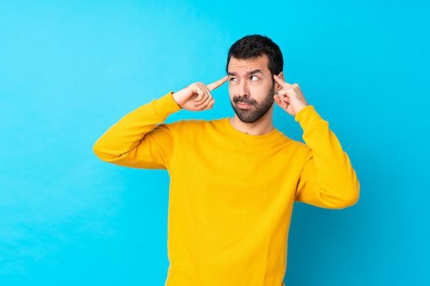 Giovane uomo caucasico sopra la parete blu isolata che ha dubbi e pensiero
