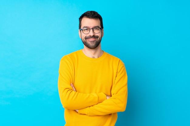 Giovane uomo caucasico sopra la parete blu isolata con gli occhiali e felice