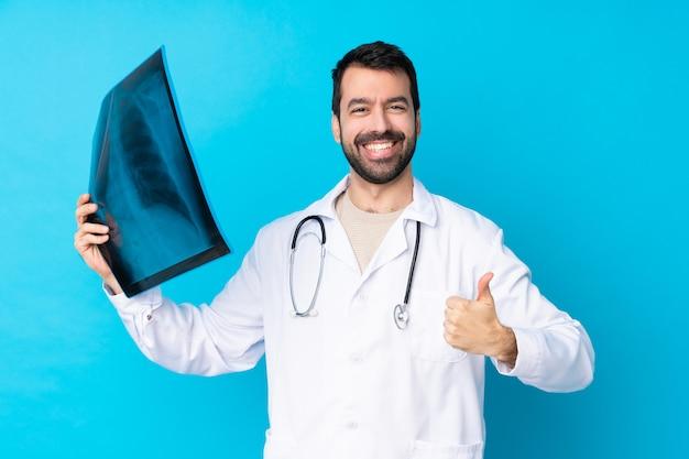 Giovane uomo caucasico sopra la parete isolata che indossa un abito medico e in possesso di una scansione ossea