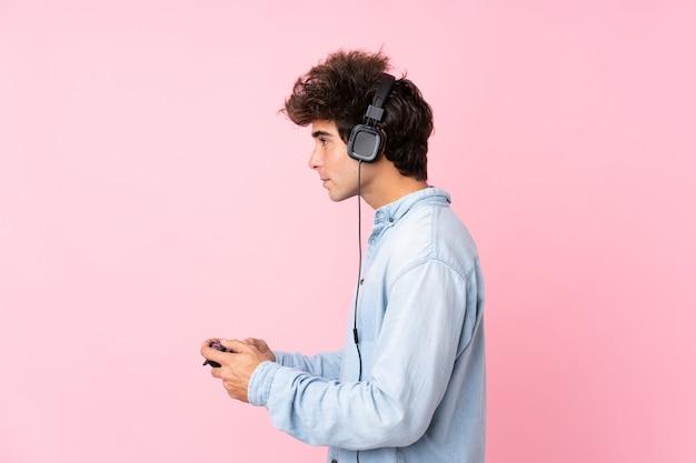 Giovane uomo caucasico sopra la parete rosa isolata che gioca ai videogiochi