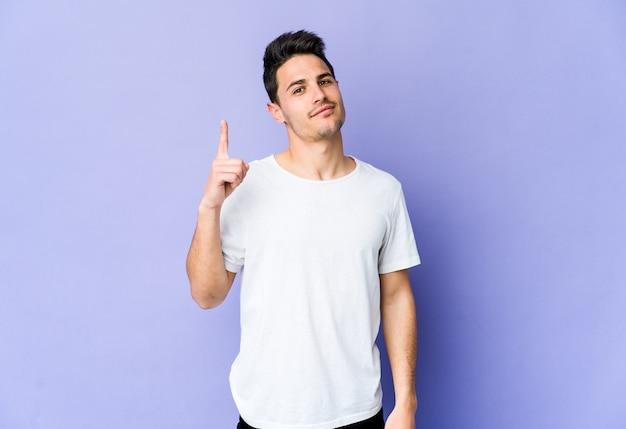 Giovane uomo caucasico sulla parete viola che mostra il numero uno con il dito.
