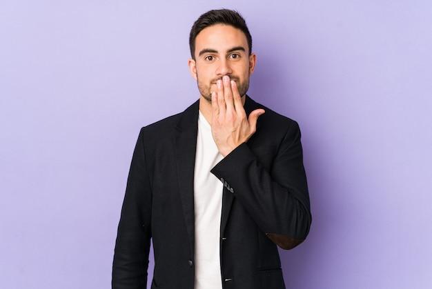 Giovane uomo caucasico sulla parete viola scioccato, coprendo la bocca con le mani