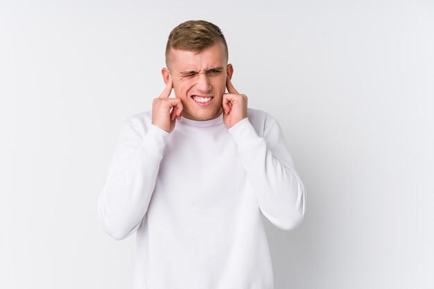 Giovane uomo caucasico sulle orecchie bianche del rivestimento murale con le mani.