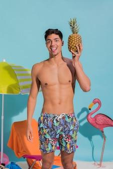 Giovane uomo che attacca la lingua e in possesso di ananas