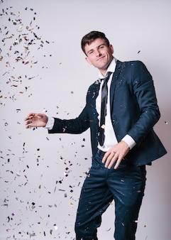 Giovane uomo che balla sotto lustrini
