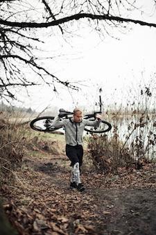 Giovane uomo che cammina con la bicicletta sul sentiero in forma