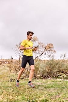 Giovane uomo che corre attraverso il campo in una gara spartana